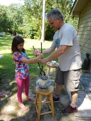 Robin Rodgers assists a camper with her horsehair pot.