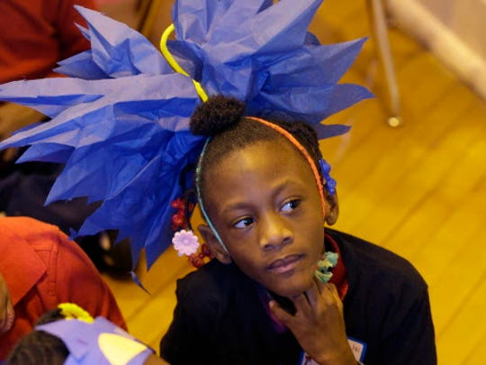 Zayna Thomas, first grader at Clarke Street School, listens to MPS Superintendent Dr. Darienne Driver reads Dr. Suess's Cat in the Hat.