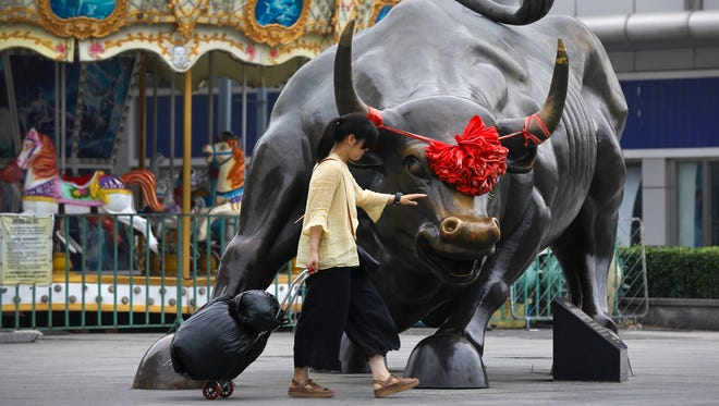 A woman pulls a 2 wheel trolley loaded with goods touches a bull statue on display outside a retail and wholesale clothing mall in Beijing, Monday, July 9, 2018. The trade war that erupted last Friday between the U.S. and China carries a major risk of escalation that could weaken investment, depress spending, unsettle financial markets and slow the global economy.