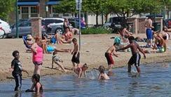 Children enjoy frolicking in Pewaukee Lake as parents