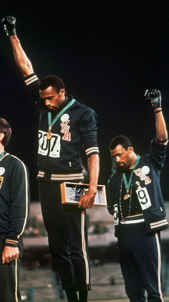 In this Oct. 16, 1968, file photo, U.S. athletes Tommie