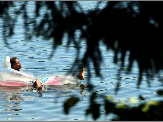 Kaseem Bell, 11, floats in Wildcat Lake on a sunny and warm Monday, July 28, 2014. (MEEGAN M. REID / KITSAP SUN)