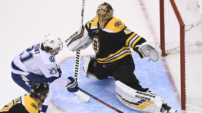 Boston Bruins goaltender Tuukka Rask (40) makes a pad save against Tampa Bay Lightning center Brayden Point (21) as Bruins center Sean Kuraly (52) looks on during the third period of an NHL hockey playoff game  Wednesday, Aug. 5, 2020 in Toronto.