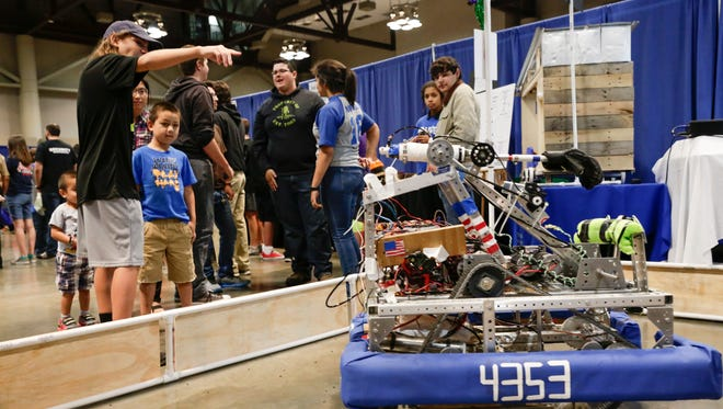 Parents and kids check out a robot on display at the David Thibodaux STEM Magnet Academy booth during the Schools of Choice Fall Frenzy in November 2016.