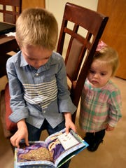 Conner Keiper, 8, reads to his younger sister, Kenleigh, 1, the afternoon of Monday, Dec. 18 in their Chambersburg home.