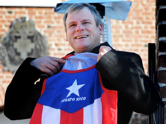 York City Mayor Michael Helfrich holds a tank top given