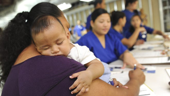 In this April 2013 file photo, 4-month-old Mack Demei Jr. takes a nap in the arms of his mother, Jasynth Demei, as she fills out forms at the Passport to Services event at the Agana Shopping Center. The outreach was hosted by the Guam Homeless Coalition and the Guam Housing and Urban Renewal Authority. The mother of three boys said she and the children have been staying at a homeless shelter for the past month and a half.