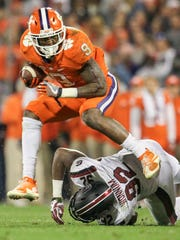 Clemson running back Wayne Gallman (9) leaps over South