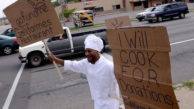 Brett Morris carries signs telling passersby about his fundraising efforst at gofundme.com Monday July 6, 2015, while some volunteers handed out flyers to cars stopped at the light at the corner of Ceder and Shiawassee streets. Morris is trying to crowdfund money to fix up a food cart so he can get his chef-for-hire business going.