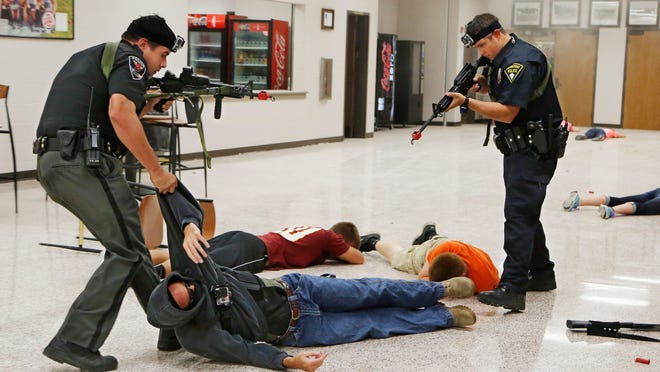 Police officers apprehend an armed man during a mock shooting demonstration as part of Active Shooter Training Thursday, August 7, 2014, at Clinton Prairie High School near Frankfort. In addition to the mock shooting demonstration, the training for police teachers, staff and others included presentations from law enforcement officers, and breakout sessions to discuss scenarios and answer questions.