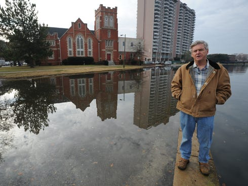 Skip Stiles, executive director of Wetlands Watch, stands on a flood wall in a neighborhood of Norfolk that is regularly flooded by high tides because of rising sea level.