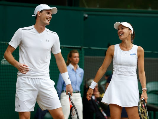 Britain's Jamie Murray and Switzerland's Martina Hingis laugh as they play Finland's Henri Kontinen and Britain's Heather Watson during the Mixed Doubles final match on day thirteen at the Wimbledon Tennis Championships in London Sunday, July 16, 2017. (AP Photo/Alastair Grant)