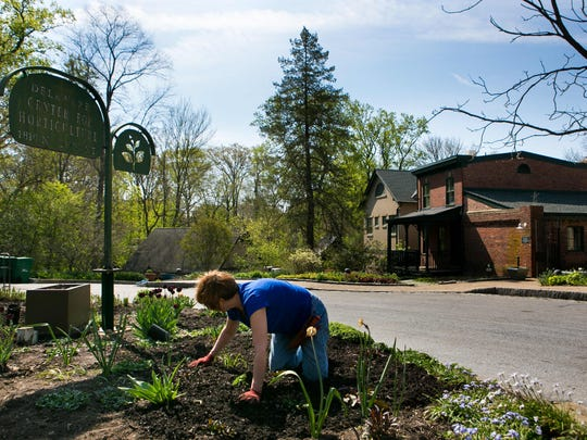 Volunteers work on the front garden area of the Delaware Center for Horticulture.
