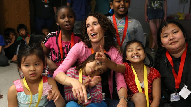 Sharilyn Rittgers, a parish nurse at Zion Evangelical Lutheran Church in Des Moines, visits with refugee children.