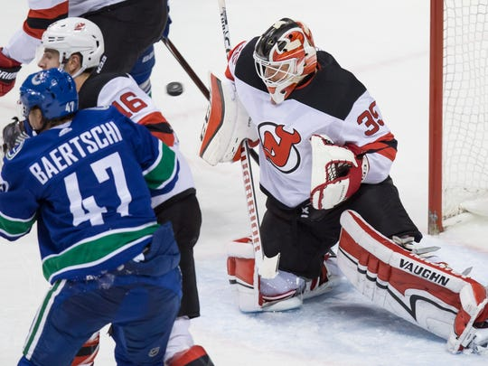 New Jersey Devils' goalie Cory Schneider, right, makes a blocker save as Steven Santini (16) battles Vancouver Canucks' Sven Baertschi, of Switzerland, during the second period of an NHL hockey game in Vancouver, British Columbia, Wednesday, Nov. 1, 2017. (Darryl Dyck/The Canadian Press via AP)