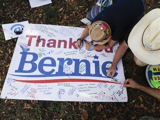 Supporters of Sen. Bernie Sanders, I-Vt., write comments on a sign following a protest march through downtown on Sunday, July 24, 2016, in Philadelphia. The Democratic National Convention starts Monday in Philadelphia.