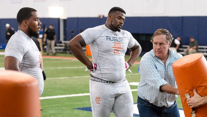 Patriots coach Bill Belichick instructs Gabe Wright and Angelo Blackson.