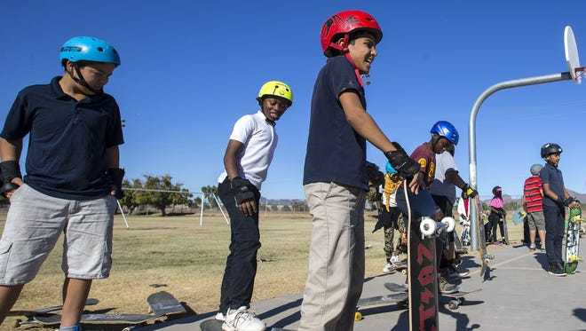 Ali Al-Shawi (red helmet), 11, holds his new skateboard during Skate After School at David Crockett Elementary School on Dec. 13, 2017, in Phoenix. Cowtown Skateboards is collaborating with Skate After School to allow anyone to buy complete skateboards at a discounted price for schoolchildren, who will receive them for free.