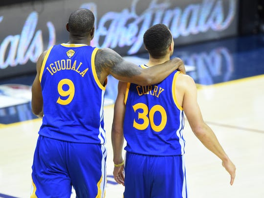 Andre Iguodala and Stephen Curry look on from the court