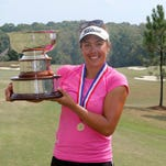 Lauren Greenlief of Oakton, Virginia, holds the championship trophy from the USGA Women's Mid-Amateur Championship at Squire Creek.