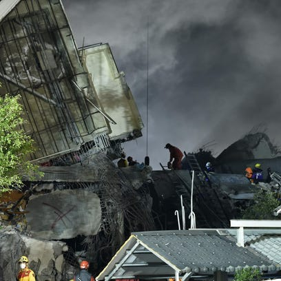Rescuers work over rubble at the site of a collapsed