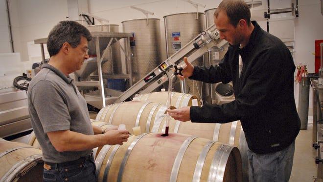 Tony Giovingo left) and Jordan Klass pull a sample of wine at the Northwest Wine Stud