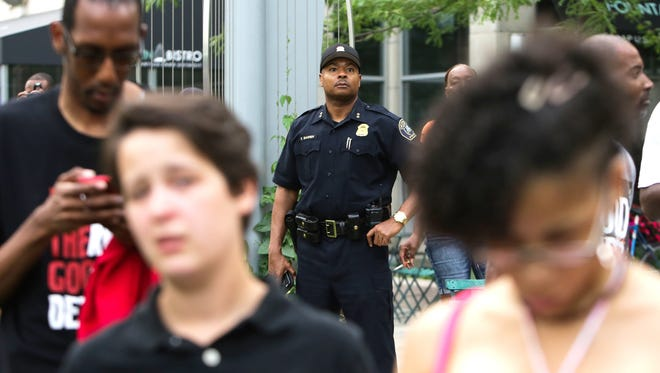 Detroit police Commander Elvin Barren looks over a crowd at Campus Martius in downtown Detroit on Friday, waiting for the start of a protest against recent shootings involving police officers.