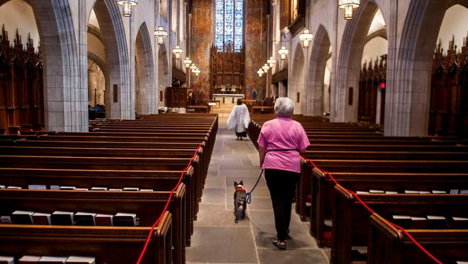 Nancy Muenchausen and her dog, Dehlia, make their way to a service of remembrance for beloved pets at Christ Church Cranbrook in Bloomfield Hills on Sunday. The service was meant to help humans heal spiritually from their loss. Separately, 73 living pets were blessed.