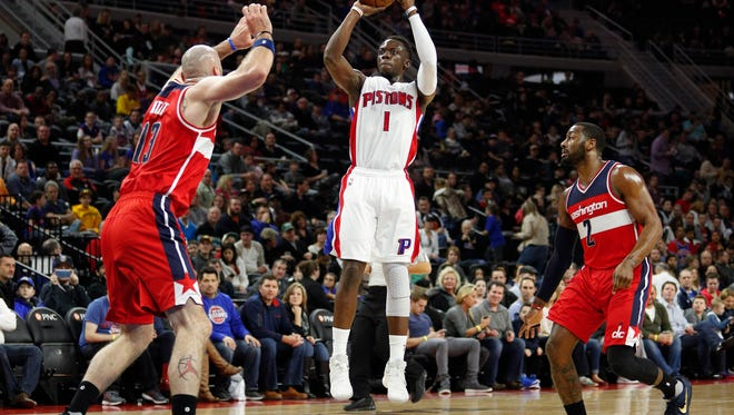 Pistons guard Reggie Jackson (1) takes a shot between Wizards center Marcin Gortat (13) and guard John Wall (2) during the first quarter Saturday at the Palace.