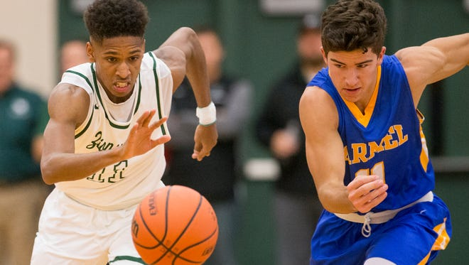 Isaiah Thompson (left), of Zionsville High School, tracks down a ball he stole from Luke Heady of Carmel High School, Carmel at Zionsville boys basketball, Zionsville, Tuesday, Nov. 21, 2017.