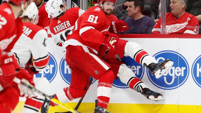 Red Wings defenseman Xavier Ouellet (61) body checks Hurricanes center Marcus Kruger (16) during the first period on Saturday, Jan. 20, 2018, at Little Caesars Arena.