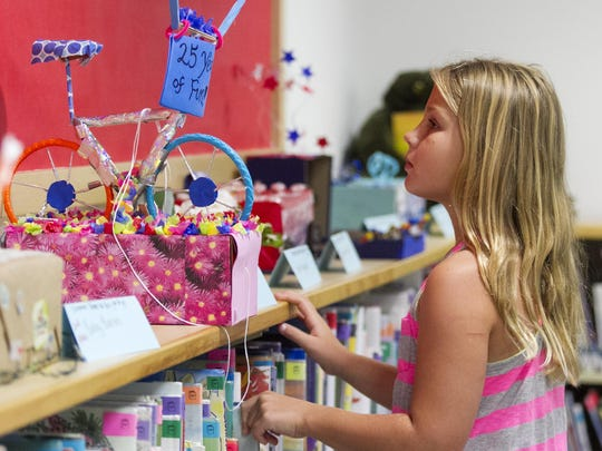 """Katelyn McCullough looks at the entries in the 13th Annual Mini Parade Float Contest at the Sanibel Library. This year's theme was """"For the Fun of It. 25 Years."""""""