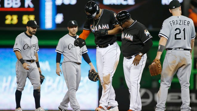 Giancarlo Stanton, center, is helped off the field by third base coach Lenny Harris after straining his groin against the Chicago White Sox. The Marlins slugger will miss the rest of the season.