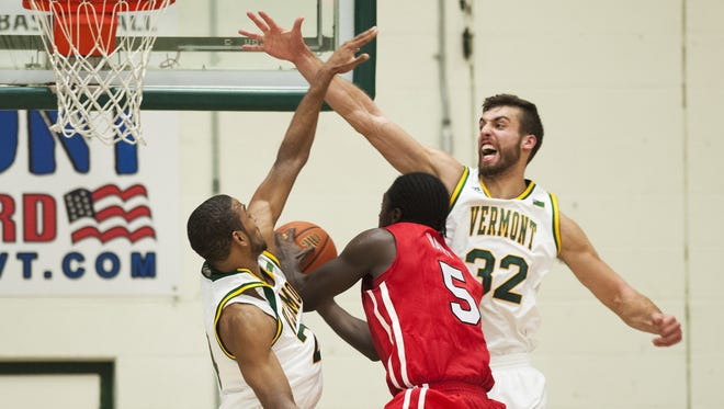 Catamounts Forward Ethan O'Day (32) and Catamounts Guard Dre Wills (24) try to block a shot by Marist's Khallid Hart (5) during the men's basketball game between the Marist Red Foxes and the Vermont Catamounts at Patrick Gym on Sunday afternoon in Burlington.