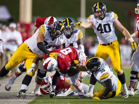 Indiana running back Jordan Howard (8) is brought down by a host of Iowa defenders during the second half of an NCAA college football game in Bloomington, Ind., Saturday, Nov. 7, 2015. Iowa won 35-27. (AP Photo/Doug McSchooler)