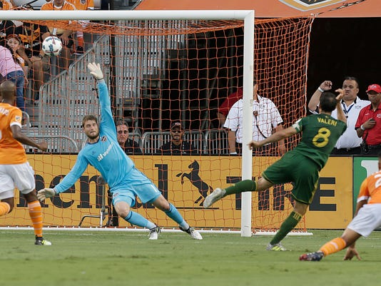 Portland Timbers midfielder Diego Valeri (8) scores a goal past Houston Dynamo goalkeeper Tyler Deric (1) during the first half of an MLS soccer match Saturday, July 29, 2017, in Houston. (Thomas B. Shea/Houston Chronicle via AP)