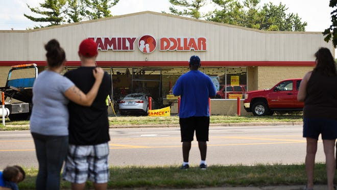 People watch as a car is hooked up to to be loaded onto a flatbed at the Family Dollar in the 900 block of W. Holmes, Saturday afternoon, Aug. 4, 2018, where a car crashed into the store.