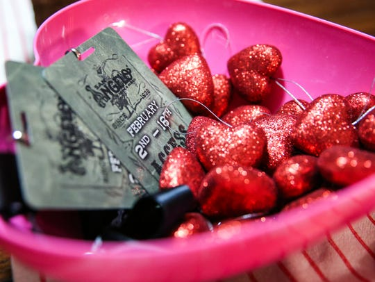 Volunteer passes sit in a basket with Valentine's Day