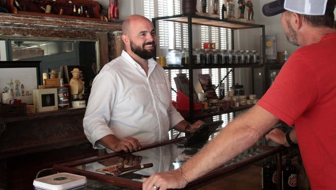 Friday Ellis, owner Governor's Cigar & Pipe, talks with customer Cade Reynolds at the Garden District shop.