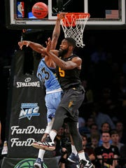 The FanDuel logo is visible, below, as Marquette guard Jajuan Johnson (23) defends Arizona State forward Obinna Oleka (5) during NCAA college basketball game in the FanDuel Legends Classic championship, Tuesday, Nov. 24, 2015, in New York.