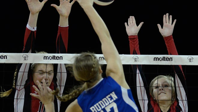 Newman Catholic's Mariah Whalen (10) and Taylor Jankowski (7) attempt to block a shot by Southwestern's Michelle Budden in the WIAA Division 4 championship volleyball match at the Resch Center on Saturday. Wausau Newman won in four sets.
