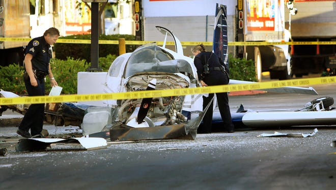 San Diego police examine the wreckage of a small plane in the parking lot of shopping center Wednesday, in San Diego.