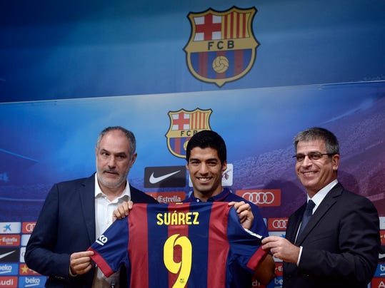 FC Barcelona's Luis Suarez, from Uruguay, center, poses with Barcelona's sports director Andoni Zubizarreta, left, and Barcelona's vice-president Jordi Mestre during a press conference of his presentation at the Camp Nou in Barcelona, Spain, Tuesday, Aug. 19, 2014. Barcelona unveiled Suarez on Tuesday, an event delayed for over five weeks since his transfer from Liverpool due to his latest suspension for biting an opponent at the World Cup. (AP Photo/Manu Fernandez)