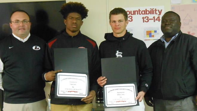 """At the February school board meeting, Principal John Barnes recognized seniors Daylon Burks and Jonathan Walley for signing with PRCC's Wildcat football team. Pictured, from left, are Coach Zach Jones, Burks, Walley and Barnes. Jones was also honored as """"Coach of the Year"""" and Burks as """"Player of the Year."""""""