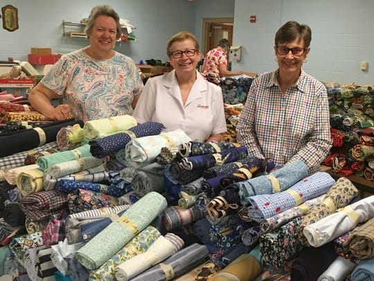 Rolls of fabric fill a table at the York Salvation