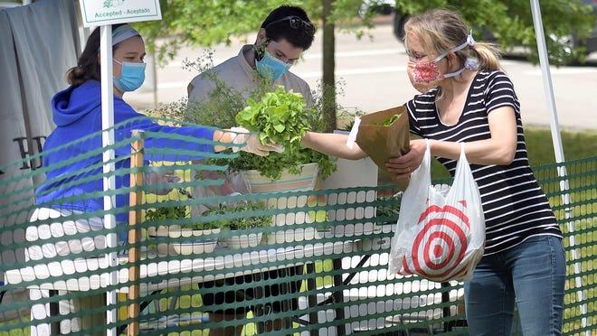 Ami Faugno of Sturbridge, right, purchases a head of lettuce from Lena Voghel and John Dalterio, owners of the Window Box Farm of Tolland, CT, at the Sturbridge Farmer's Marker, held June 7 on the Sturbridge Common.