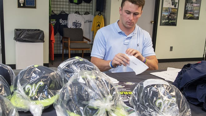 Bravehearts player J.P. Barry works in the team office Tuesday, preparing the distribution of hats and other items for teammates this season.