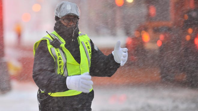 Traffic control officer Richard Graham braves the snow and cold to  direct traffic at the corner of Randolph and W. Larned as snow falls in Detroit.