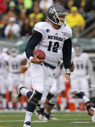 Sep 7, 2019; Eugene, OR, USA;  Nevada Wolf Pack quarterback Carson Strong (12) scrambles for a first down against the Oregon Ducks in the first half at Autzen Stadium. Mandatory Credit: Jaime Valdez-USA TODAY Sports