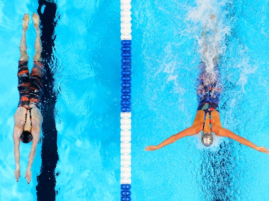 Kelsi Worrell, left, races Dana Vollmer, right, during the women's 100-meter butterfly final at the U.S. Olympic swimming trials, Monday, June 27, 2016, in Omaha, Neb. Worrell won the race and Vollmer finished in second place. (AP Photo/Mark J. Terrill)
